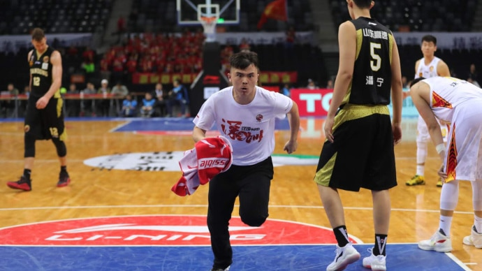 Meng Fei runs onto a basketball court, he is holding a red towel.
