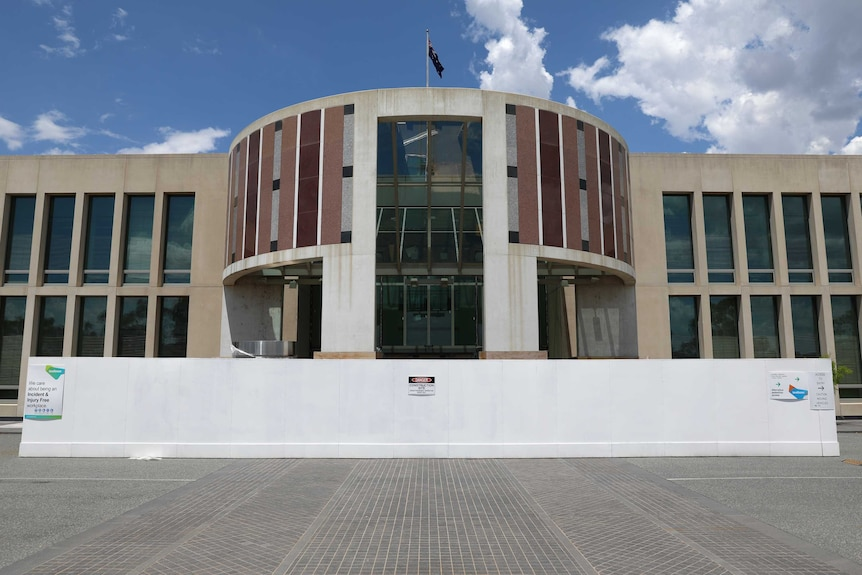 A construction fence surrounds the Senate entrance of the Parliament House building in Canberra. An Australian flag flies on top