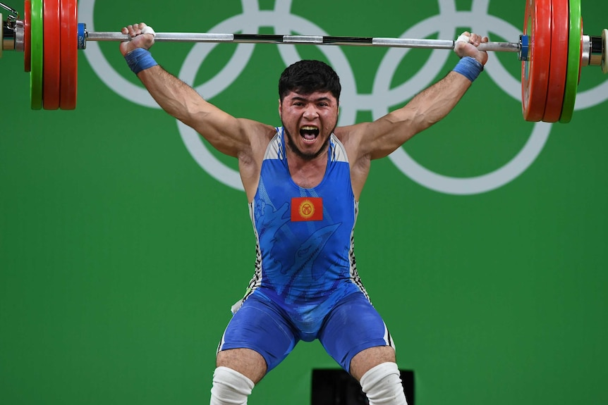 Izzat Artykov lifts weight above his head