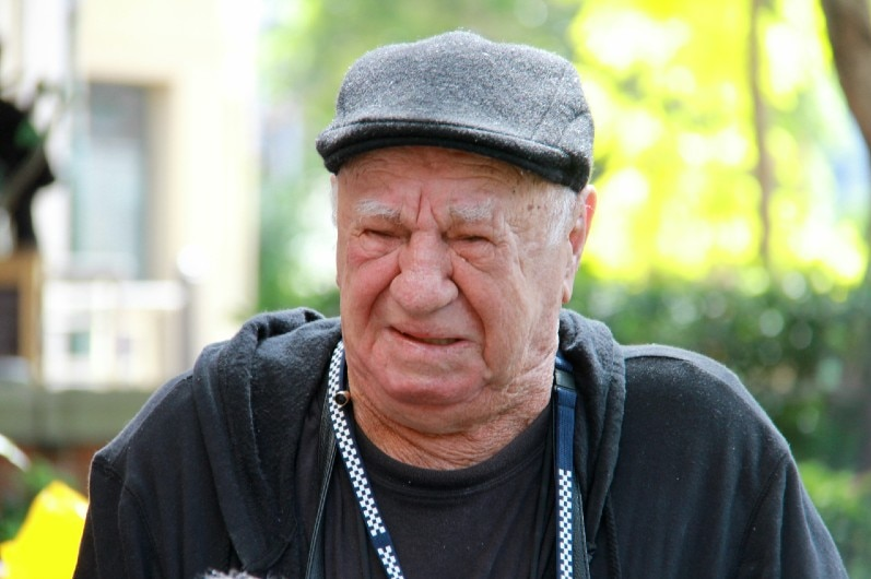 An old man in a hat crying.