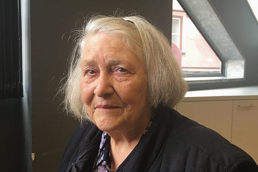 An elderly woman looks at the camera.
