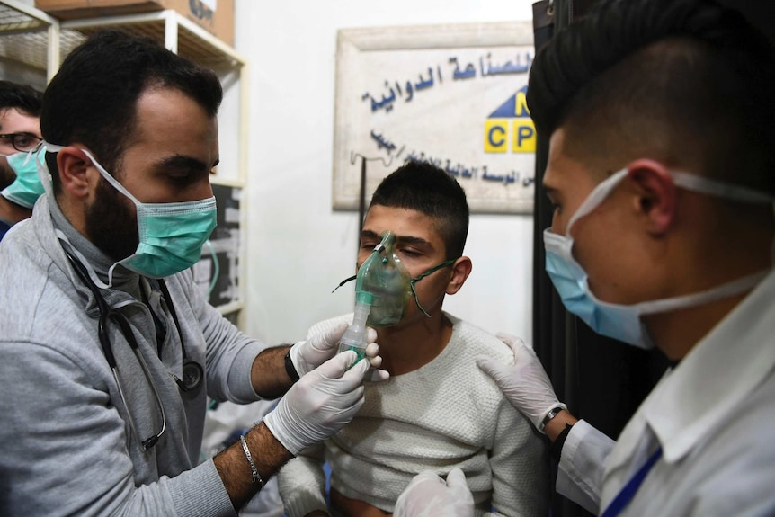 Two doctors tend to a young man wearing an oxygen mask.