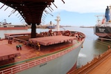 Iron ore drops from a conveyor belt into the hatch of a ship at the FMG port at Port Hedland.