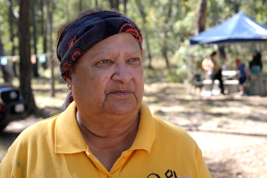 An indigenous woman wearing a headband, yellow shirt, straight face, trees and tent behind.