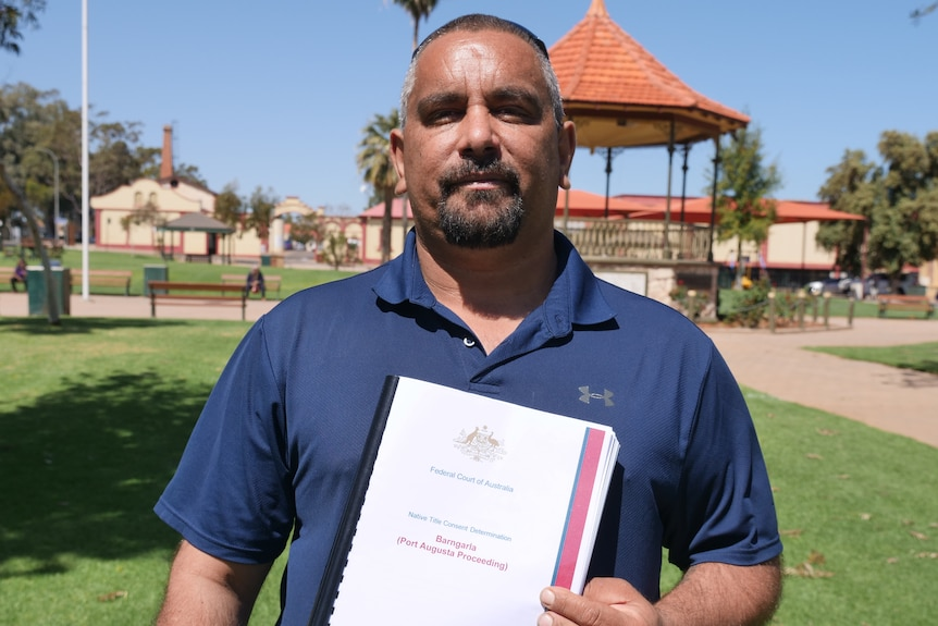 a man holding a document smiling