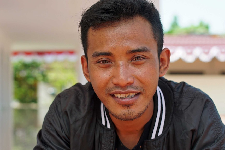 Ali Fauzi smiles looking into the camera in a close up photo of his face. He is sitting at the Peace Circle compound.