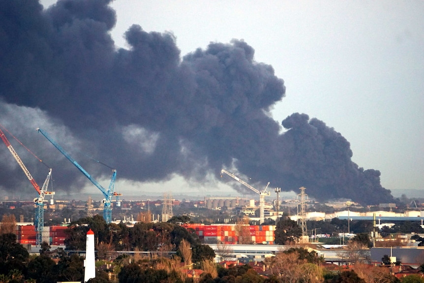 Thick black smoke fills the sky above cranes, shipping containers and industrial buildings.