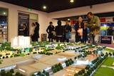 People walk past a display model of Hanya Federal's Melbourne development.