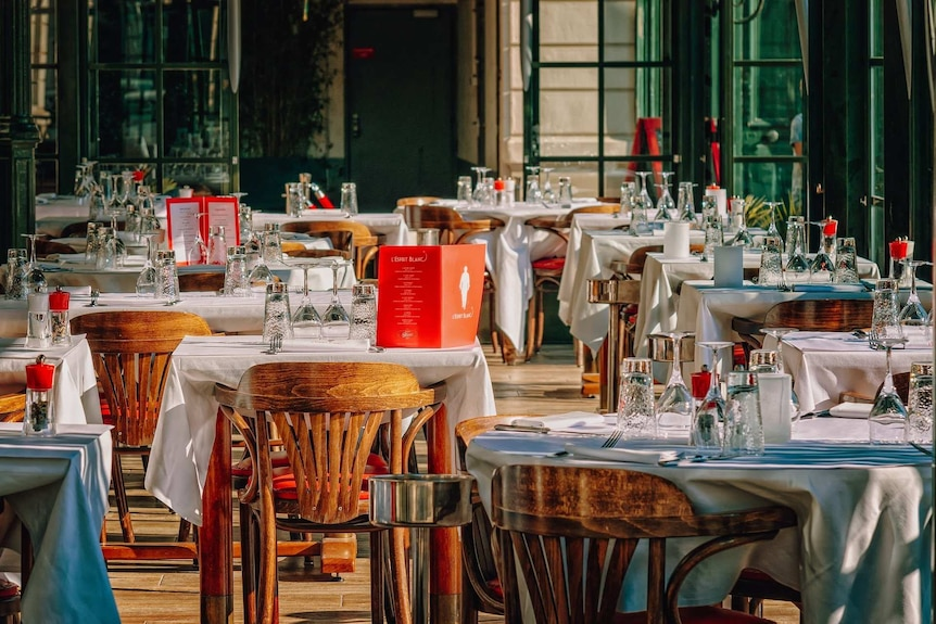 A empty restaurant with white-clothed tables set.