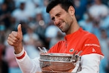 Novak Djokovic holds his thumbs up with the French Open trophy