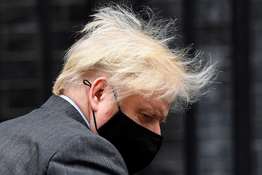 Johnson, wearing a black face mask and wild hair, looks down