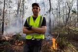 Cultural burn crew member standing at site of burn