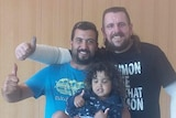 Two men and a young girl all smile and give thumbs up