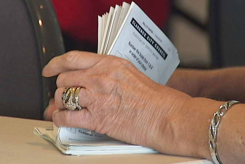 A woman counts local government ballot papers for a council election in Tasmania.