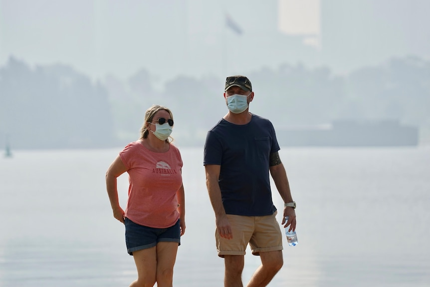 Couple walking amid the smoke on South Perth foreshore