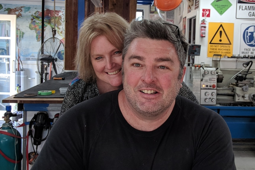 A middle-aged man and woman in a garage full of tools and machinery.