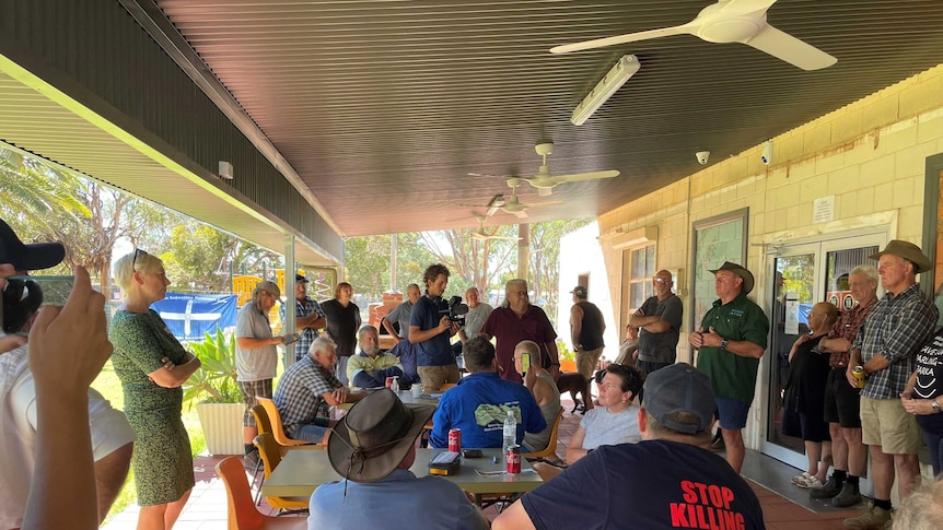 A large group of Menindee locals gathered under a shaded building space, with one man speaking to the assembled group