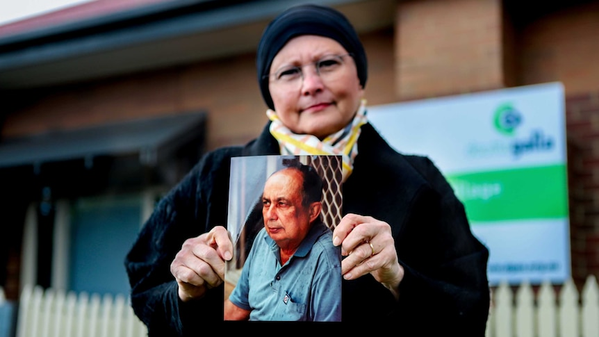 Woman in black coat and scarf wearing glasses stands outside aged care home holding photo of her father