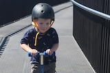 A little boy scoots along a path, smiling.
