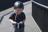 A little boy scoots along a path, smiling.