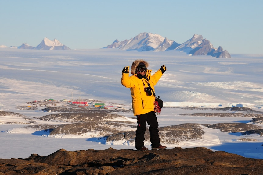 Antarctic expeditioner gesturing outside.