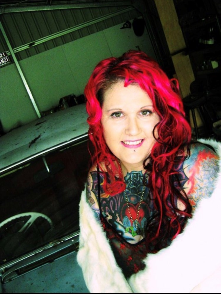 A woman with bright pink hair and large, colourful tattoos smiling