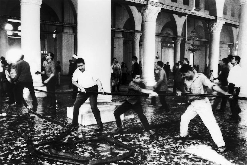 A line of men hoist a fire hose inside the Mosque
