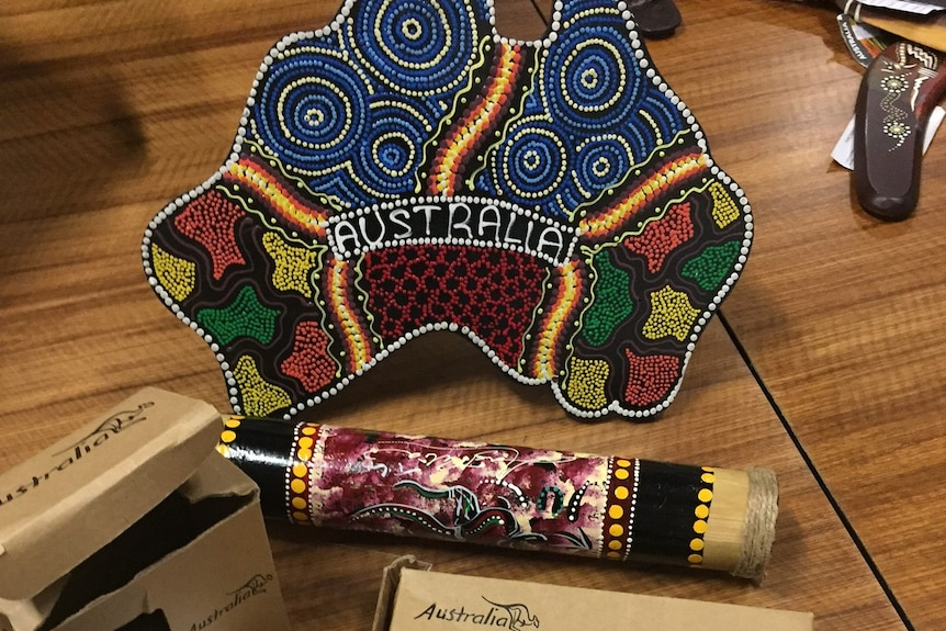 Fake Aboriginal-style souvenirs in a shop, including a plate in the shape of Australia