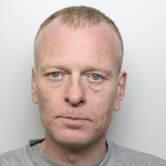 A white middle-aged man with short light-coloured hair looks into the camera with a neutral expression on his face