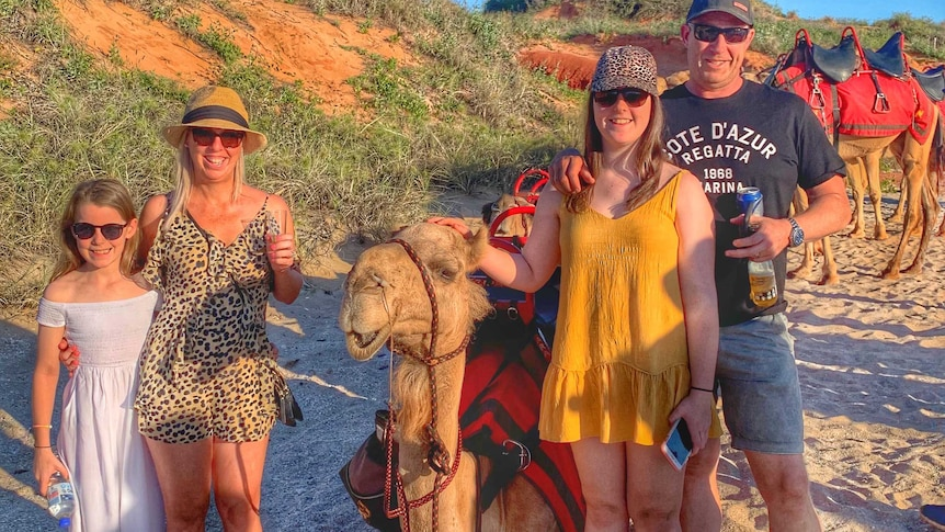 A family of four pose with a camel with drinks in their hands.