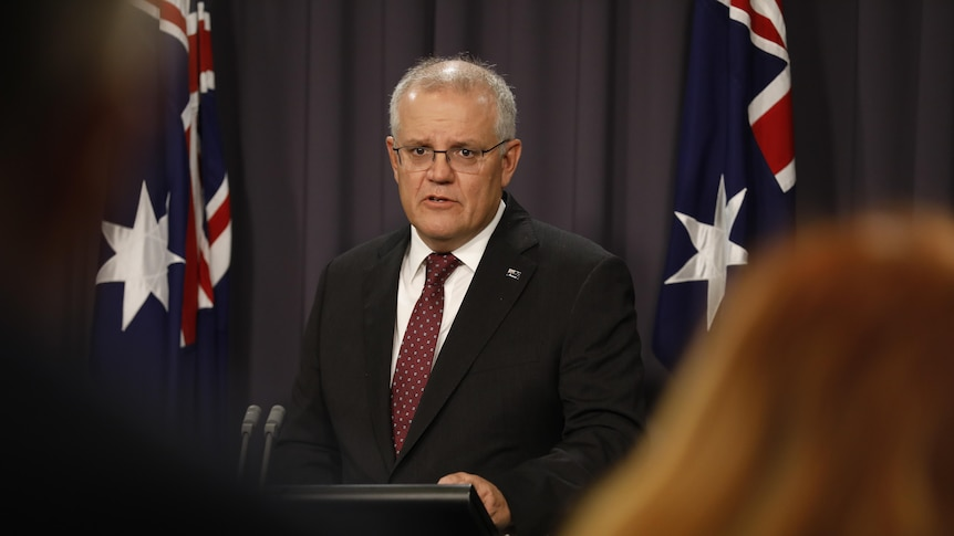 Prime Minister Scott Morrison speaking in front of a lectrern with two Australian flags behind him.