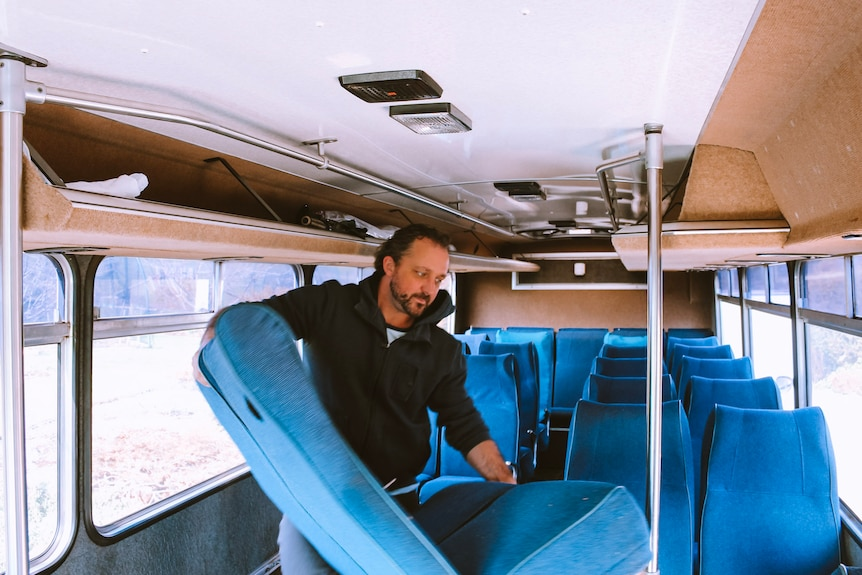 Kevin Craft holds a seat from a bus, which he converted into a mobile home for his family.