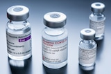 One vial of Moderna, one of AstraZeneca, and two of Pfizer are arranged on a plain grey background.