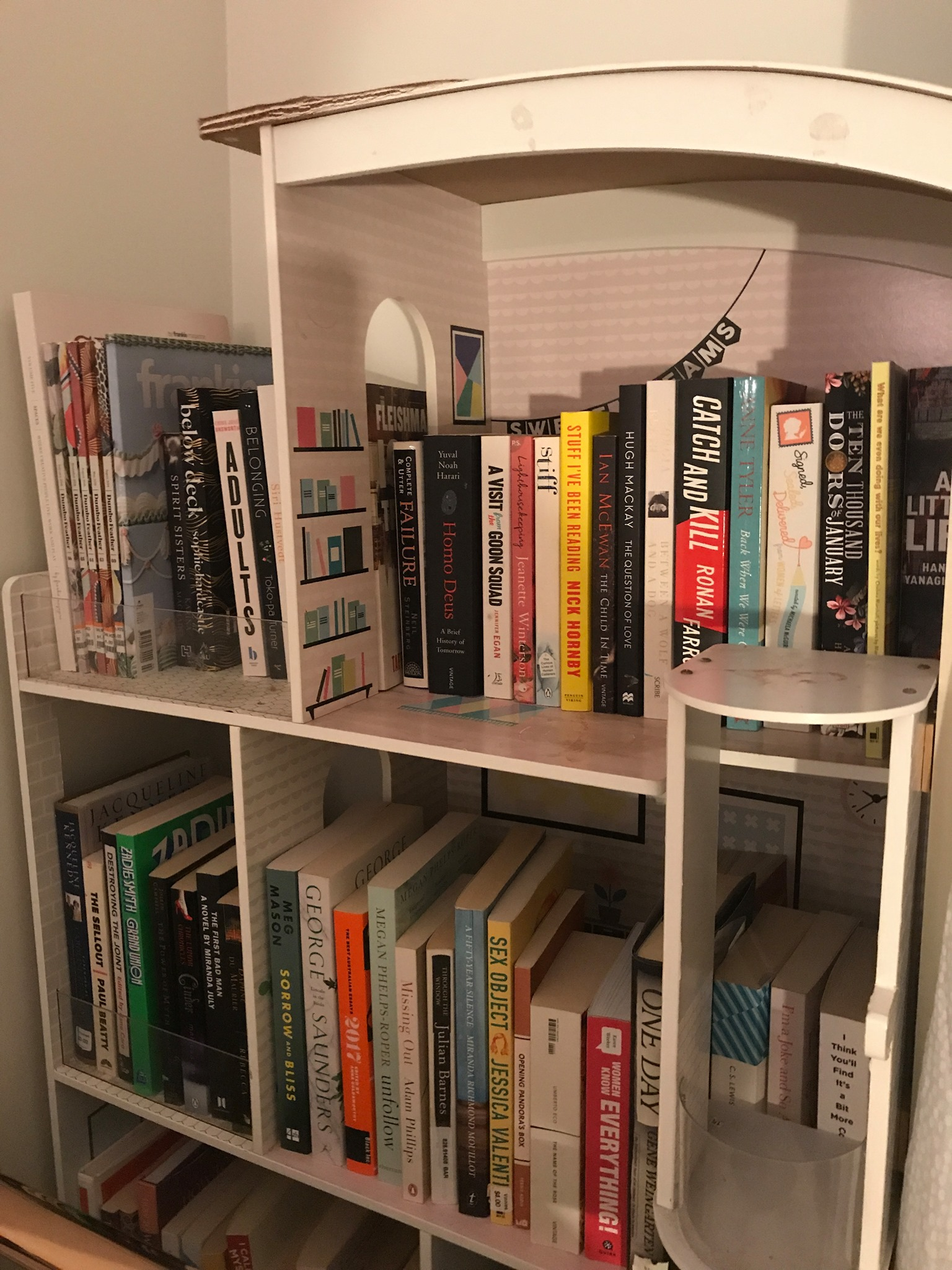 A dollhouse emptied of belongings and instead piled with books, like a bookshelf.