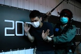A detained anti-government protester is held by a riot police officer during a march in Hong Kong.