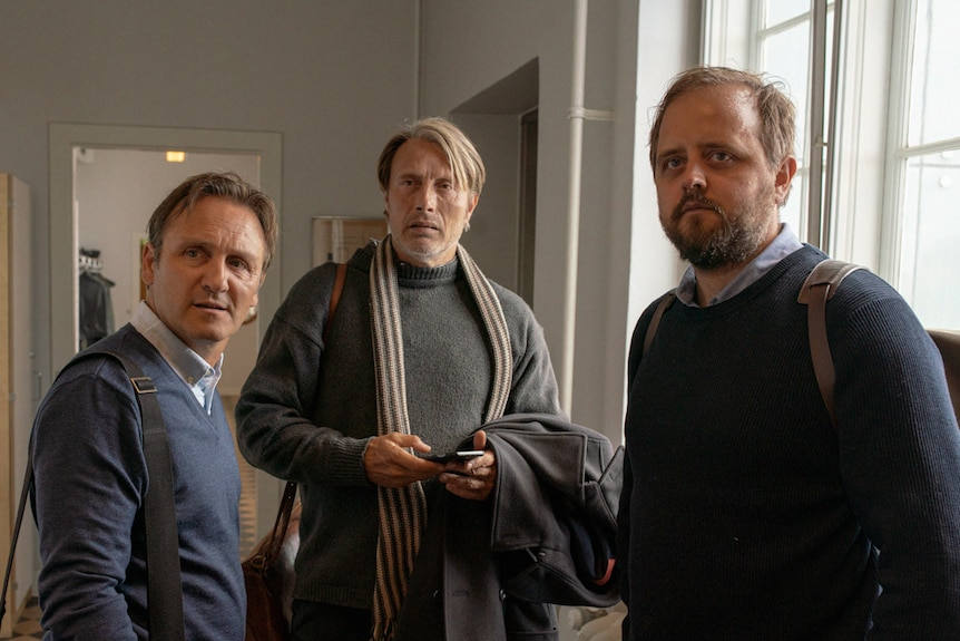 Interior shot of the three men standing together and looking in one direction as if concerned.