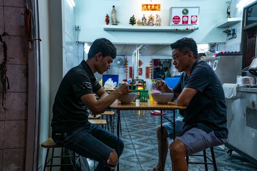 A young Laotian man and a 51-year-old Taiwanese man sit opposite each other eating, at a roadside shop.