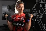 Sam Bremner holds two dumbbells inside a gym, wearing her St George Illawarra Dragons uniform.