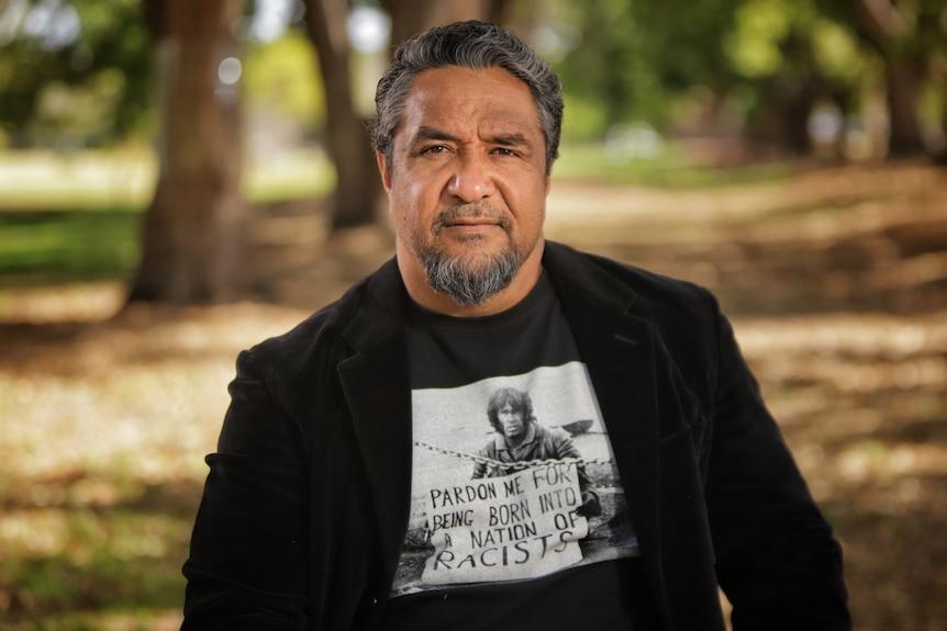 A man wearing a black shirt under a black jacket.