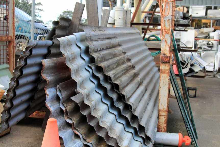 Sheets of roofing iron stacked together at the tip shop