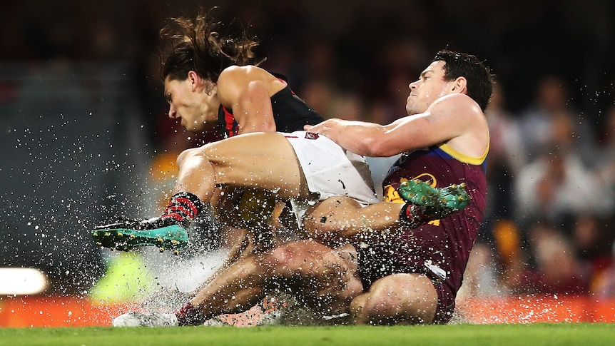 A Brisbane Lions AFL player tackles an Essendon opponent in the wet at the Gabba in Brisbane.