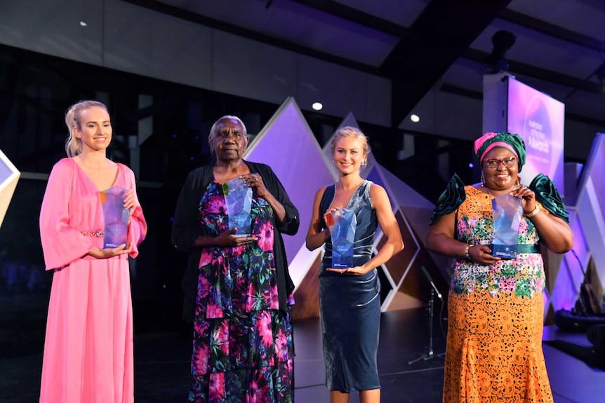 The four women smile, holding their awards on stage.