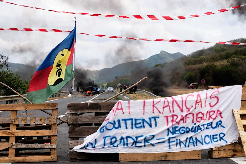 Kanaky flags wave in front of a roadblock, smoke in the distance.