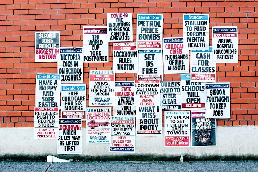 a picture of a wall of newspapers showing covid front pages
