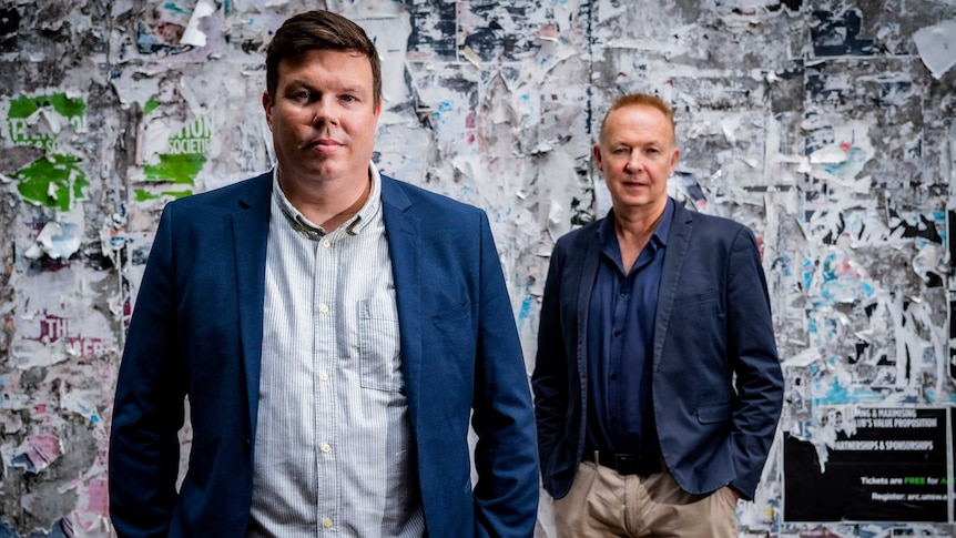 Two ben in navy blazers pose in front of a wall covered in fragments of old bill posters