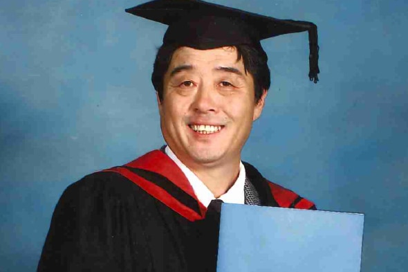 Jae-Ho Oh in a graduation gown and holding his degree.