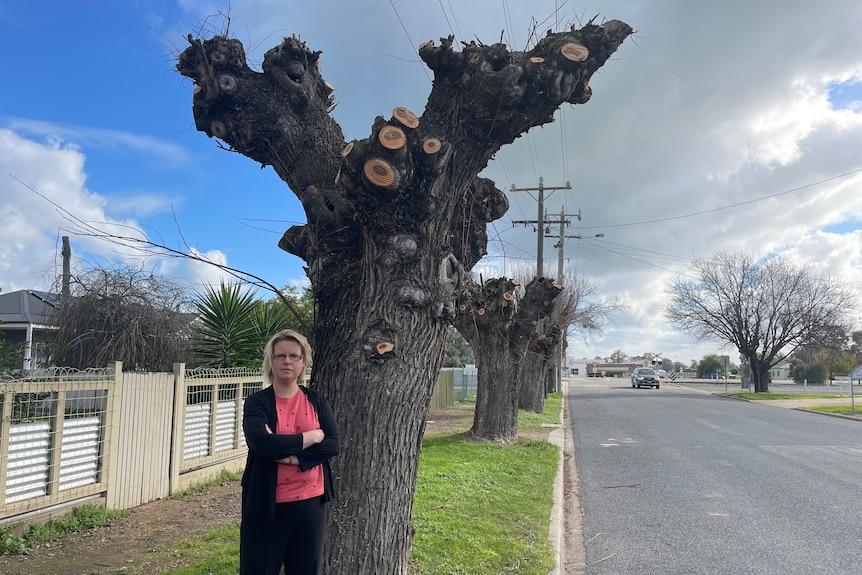 Woman stands with arms crossed in front of a tree