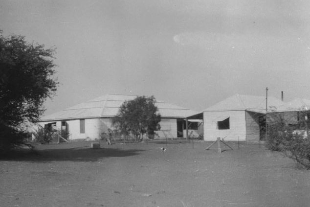 A black and white photo of a homestead on a cattle station.