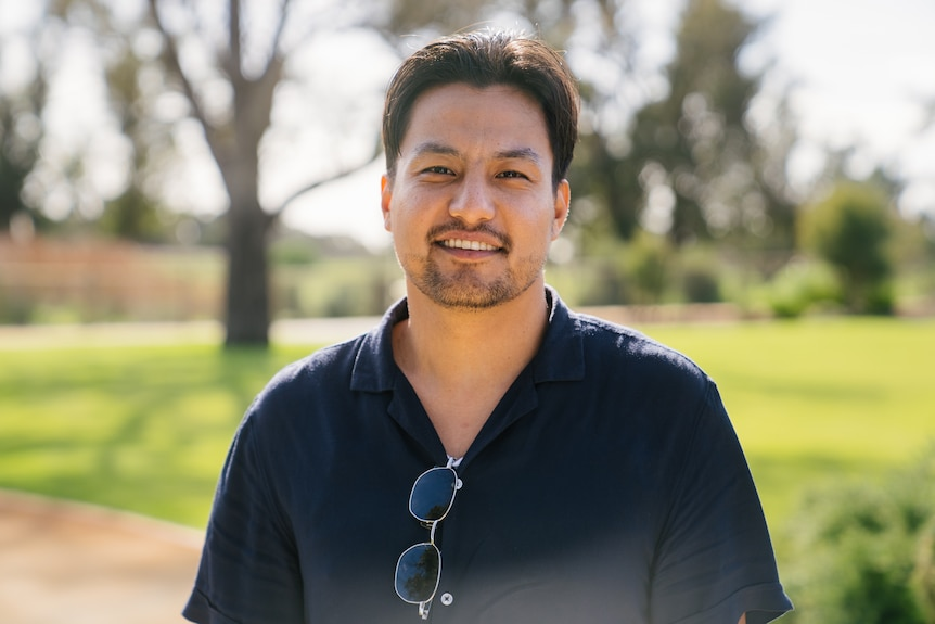 A young man stands in a sunny park, smiling at the camera. Sunglasses are hooked onto his dark polo shirt