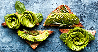 Avocado, sliced elaborately in the shape of flowers, on toast.